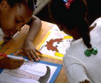 Elementary school African American girls adding long columns of big numbers